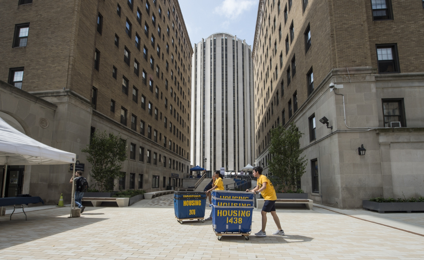 Two students in yellow shirts and blue shorts push housing cart-bins across paved plaza during move-in