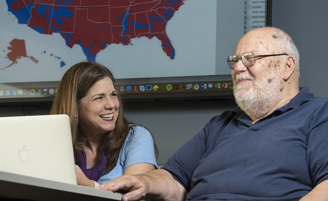 Kris and Dave Kanthak sitting at a laptop computer in front of a red-and-blue political map of the United States