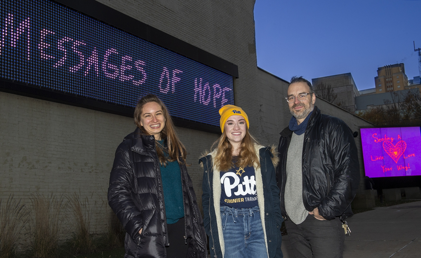 Two female students in coats and PItt gear with male faculty member outside in front of two digital screens with artwork