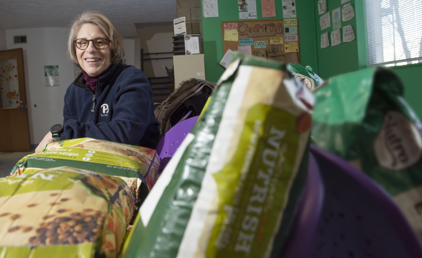 Mary Beth Rauktis wearing blue Pitt sweatshirt, shown with bags of pet food in a food pantry