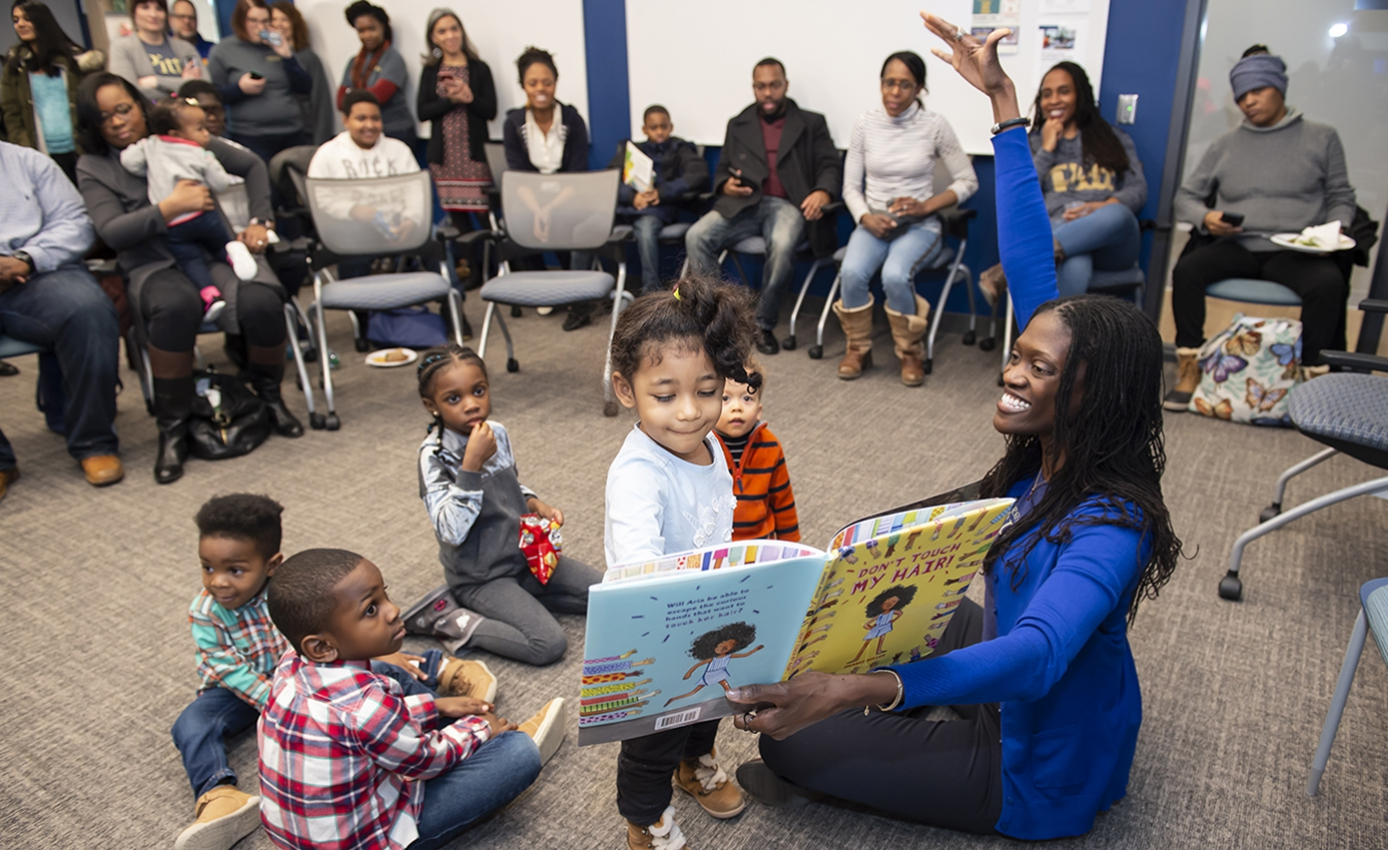 Valerie Kinloch in a blue sweater and black pants sitting in floor holding open a children's book while a group of five young children gather around her