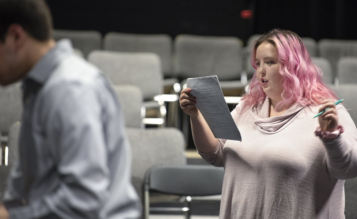 Chloe Torrence holding and reading a script and a pen in front of a theater audience section chairs