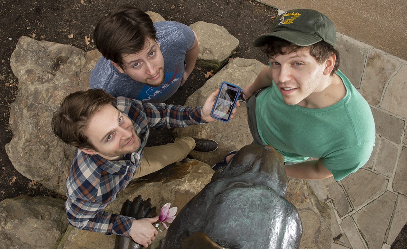 three young men looking up at the photographer, one holding a phone with the app on the screen