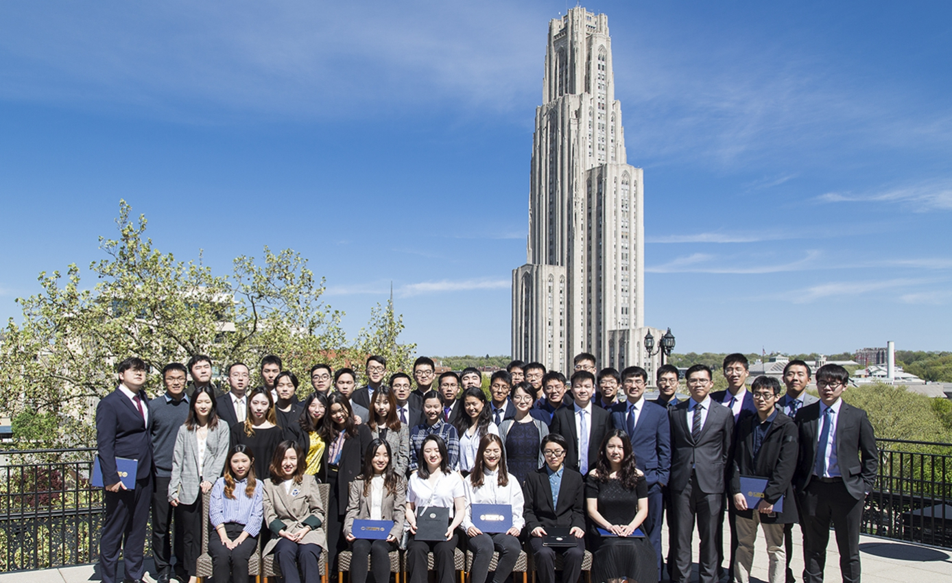 a large group of students standing together with the Cathedral in the far background