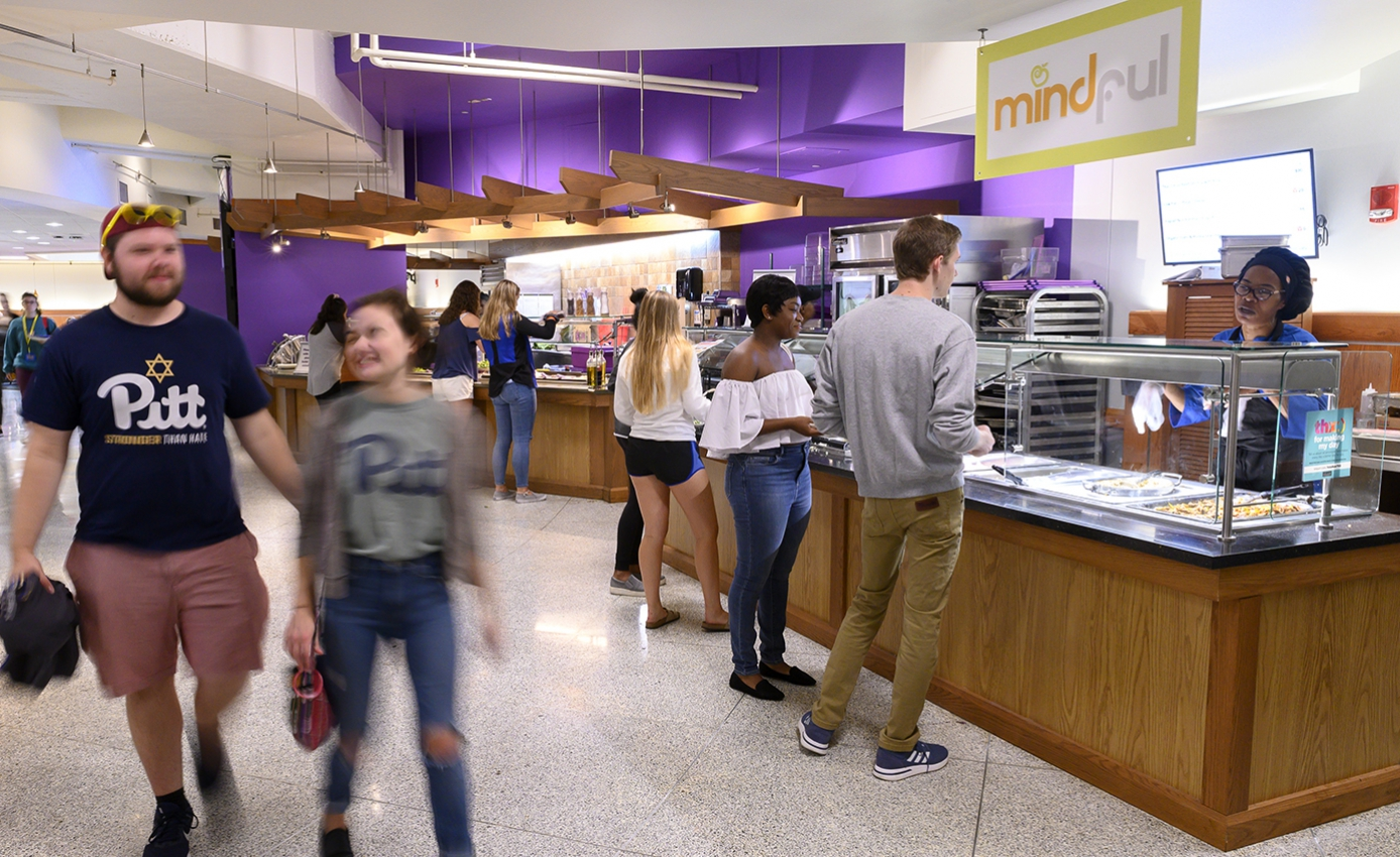 Students walking through dining hall area while other students stand at a cafeteria-style serving area