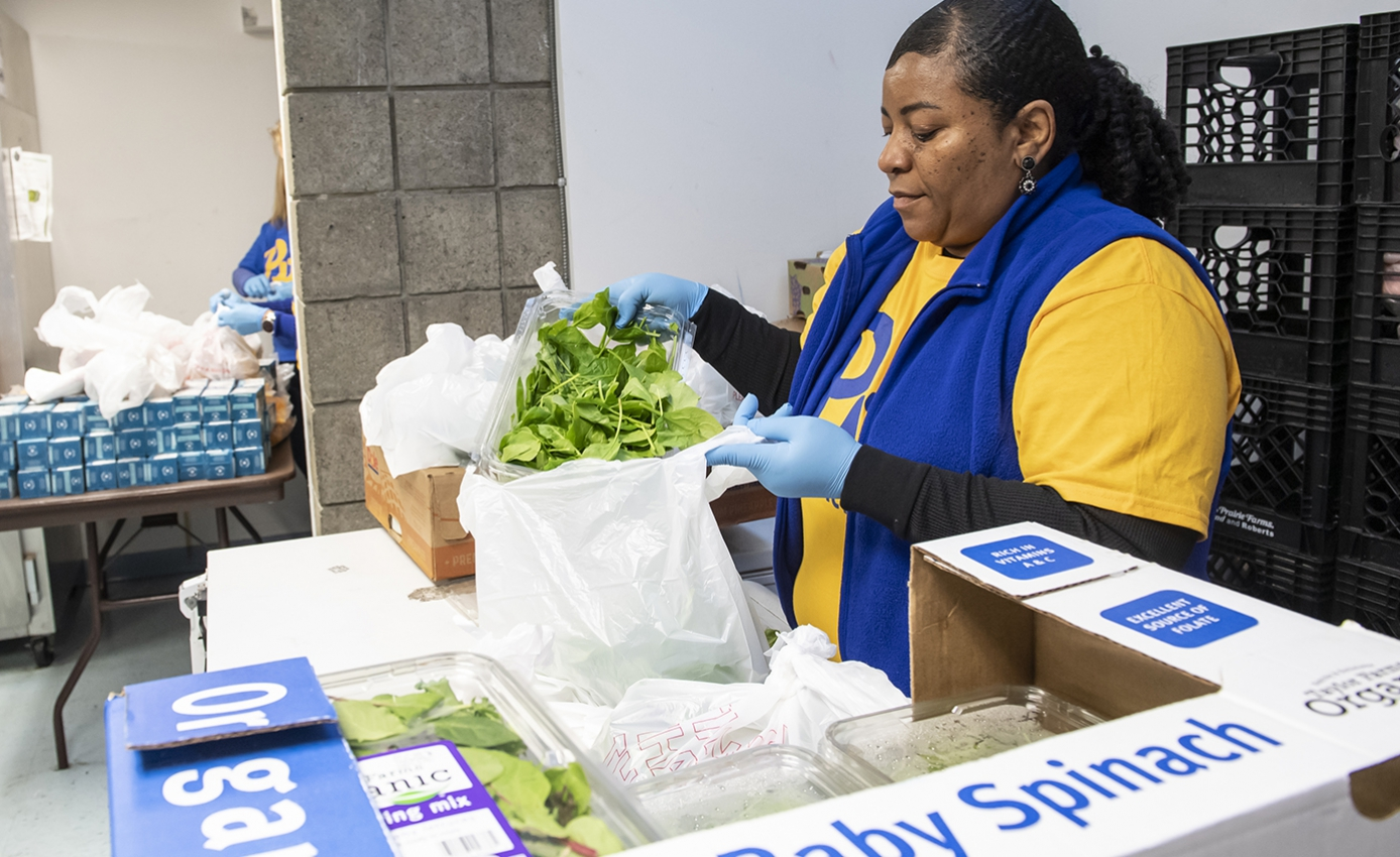 A woman in a yellow shirt and blue vest packs vegetables into a plastic bag