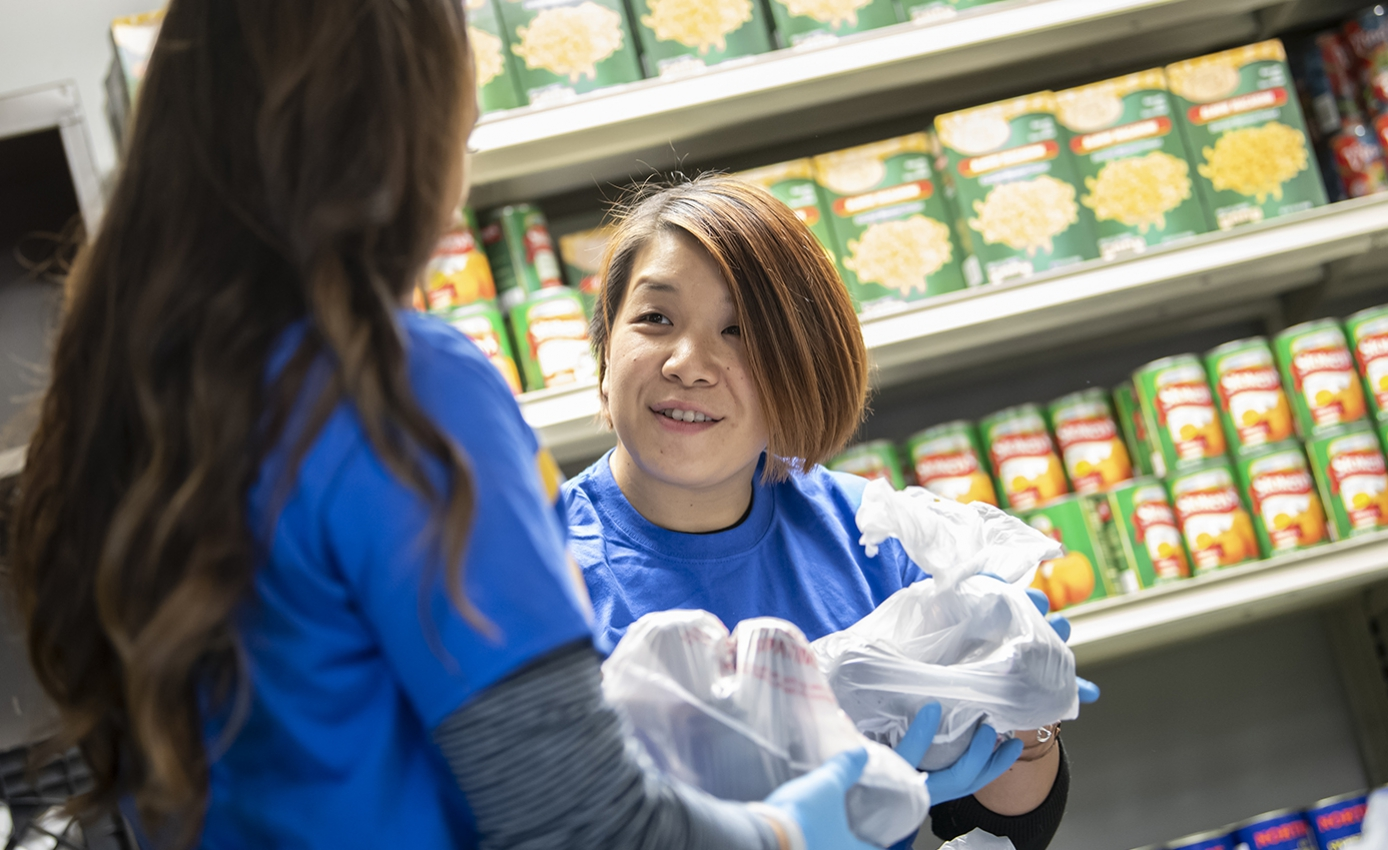 Two people in blue shirts handle groceries