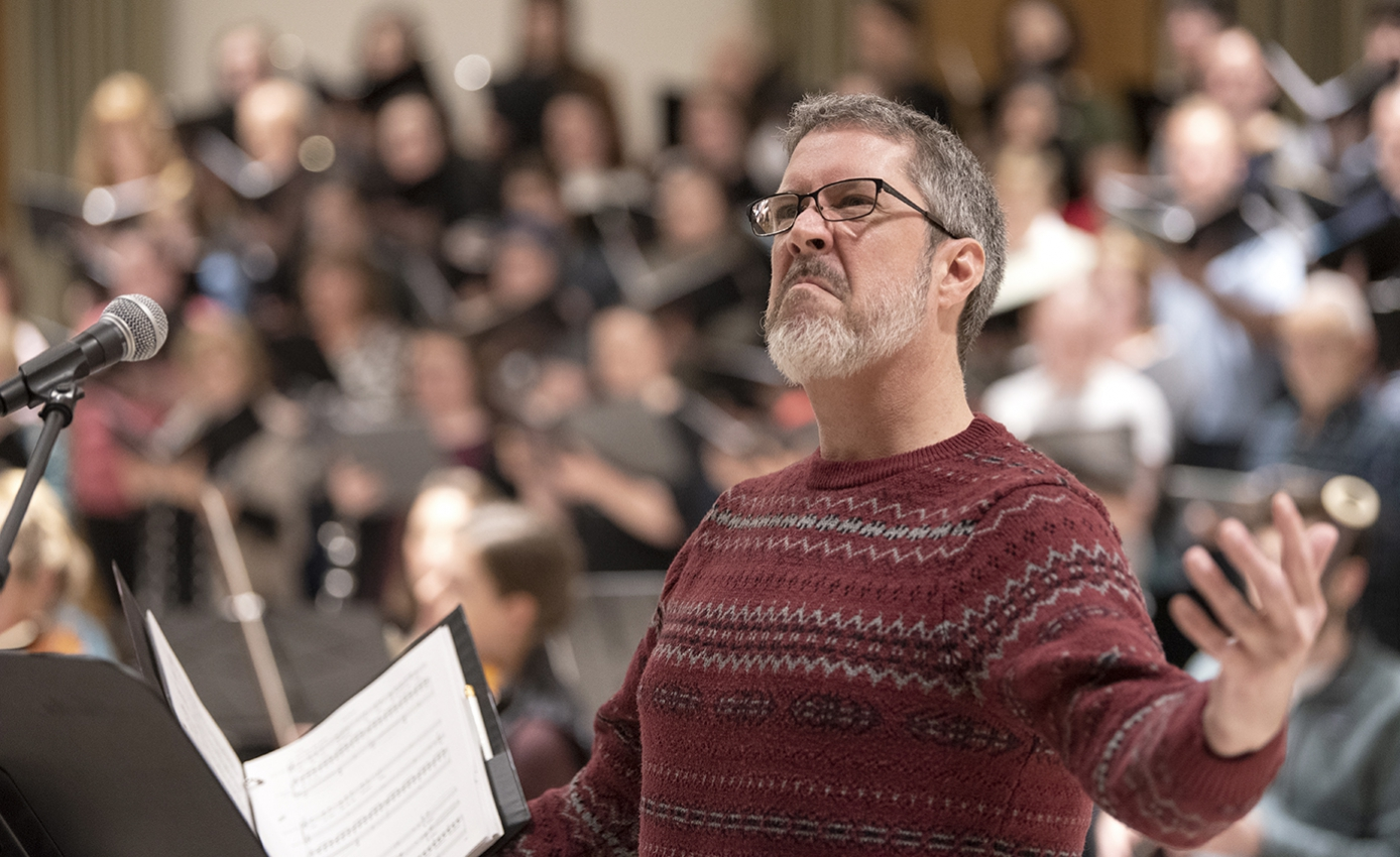 Scott O'Neal in a red sweater with his arms raised and face in a scowl, in front of a choir