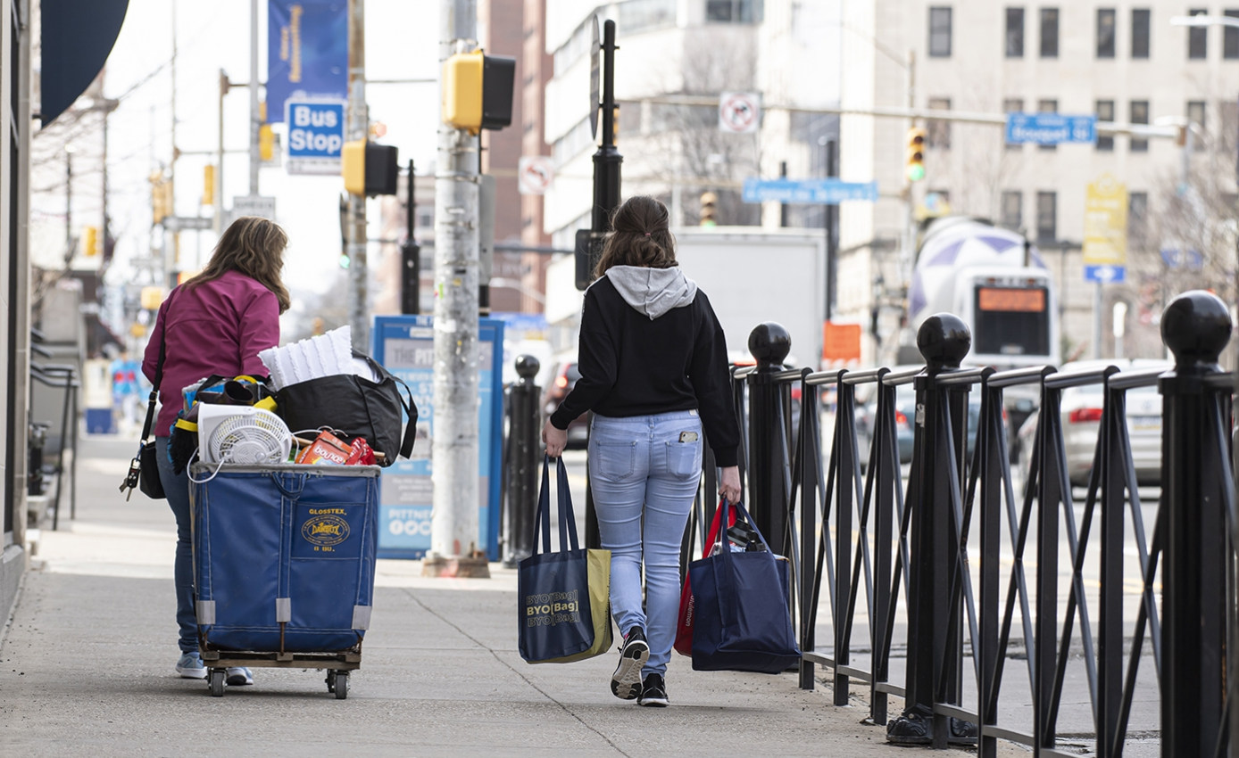 Two people walk down a sidewalk carrying luggage