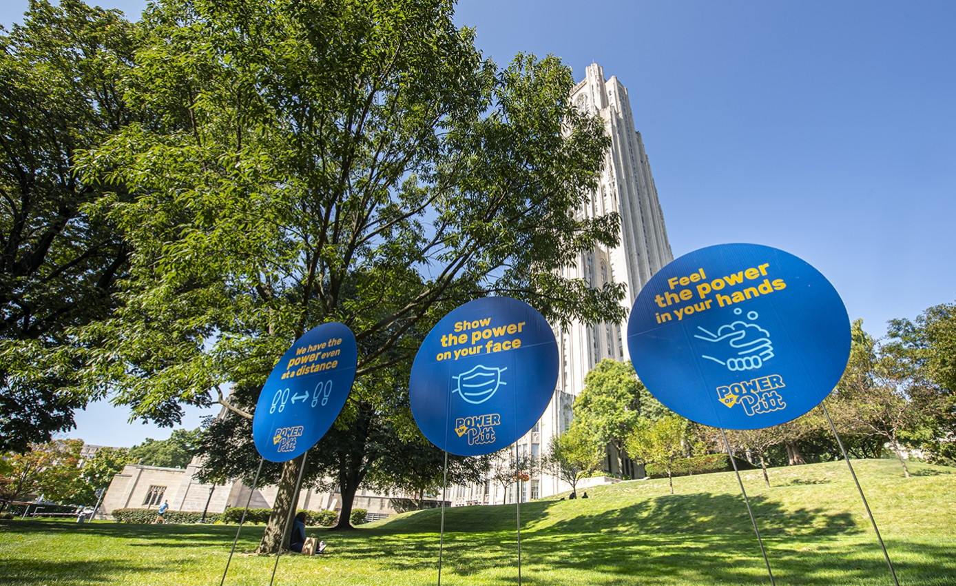 Blue signs on a lawn in front of the Cathedral of Learning