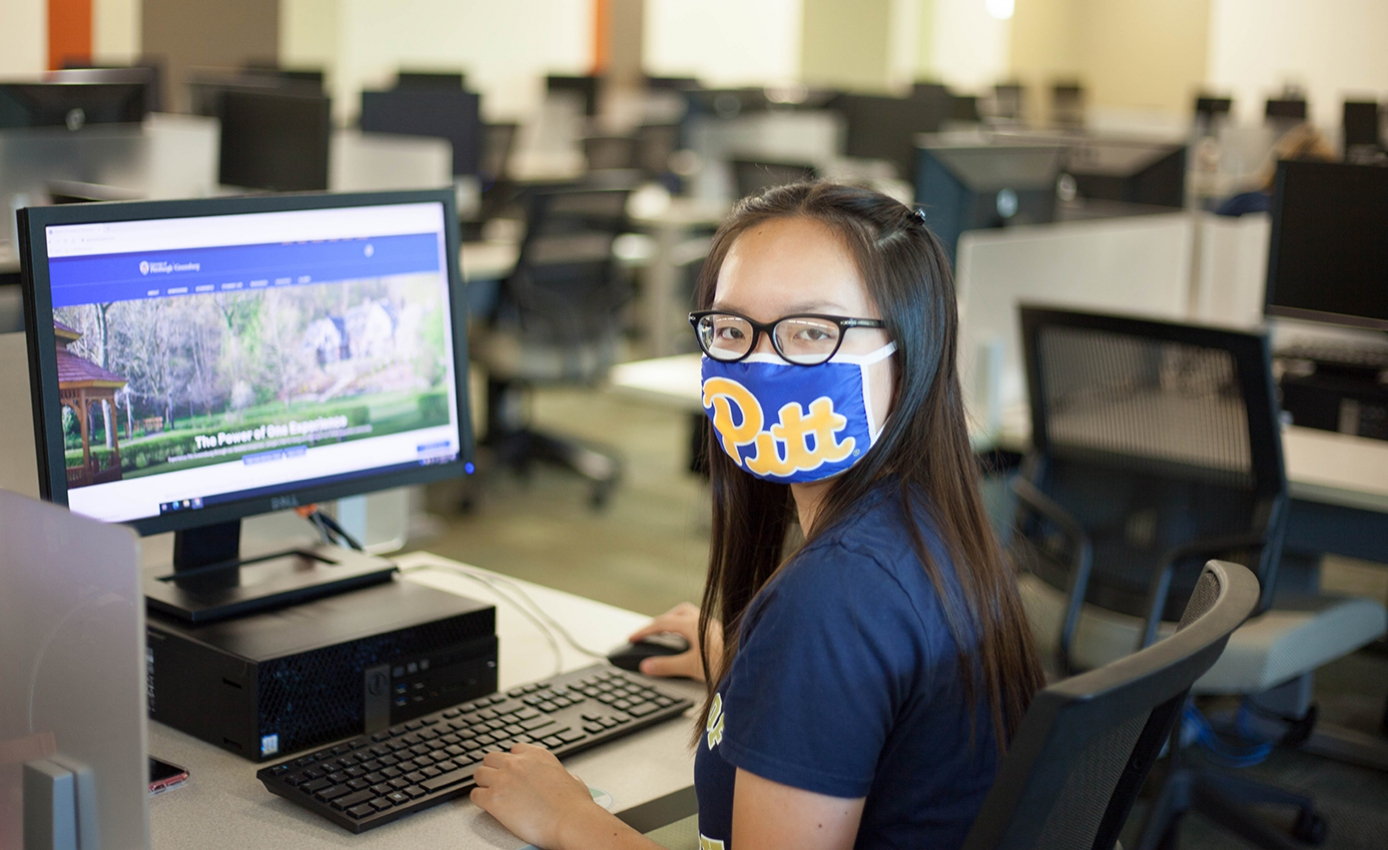 A woman in a blue Pitt face mask and shirt browses the Pitt-Greensburg website