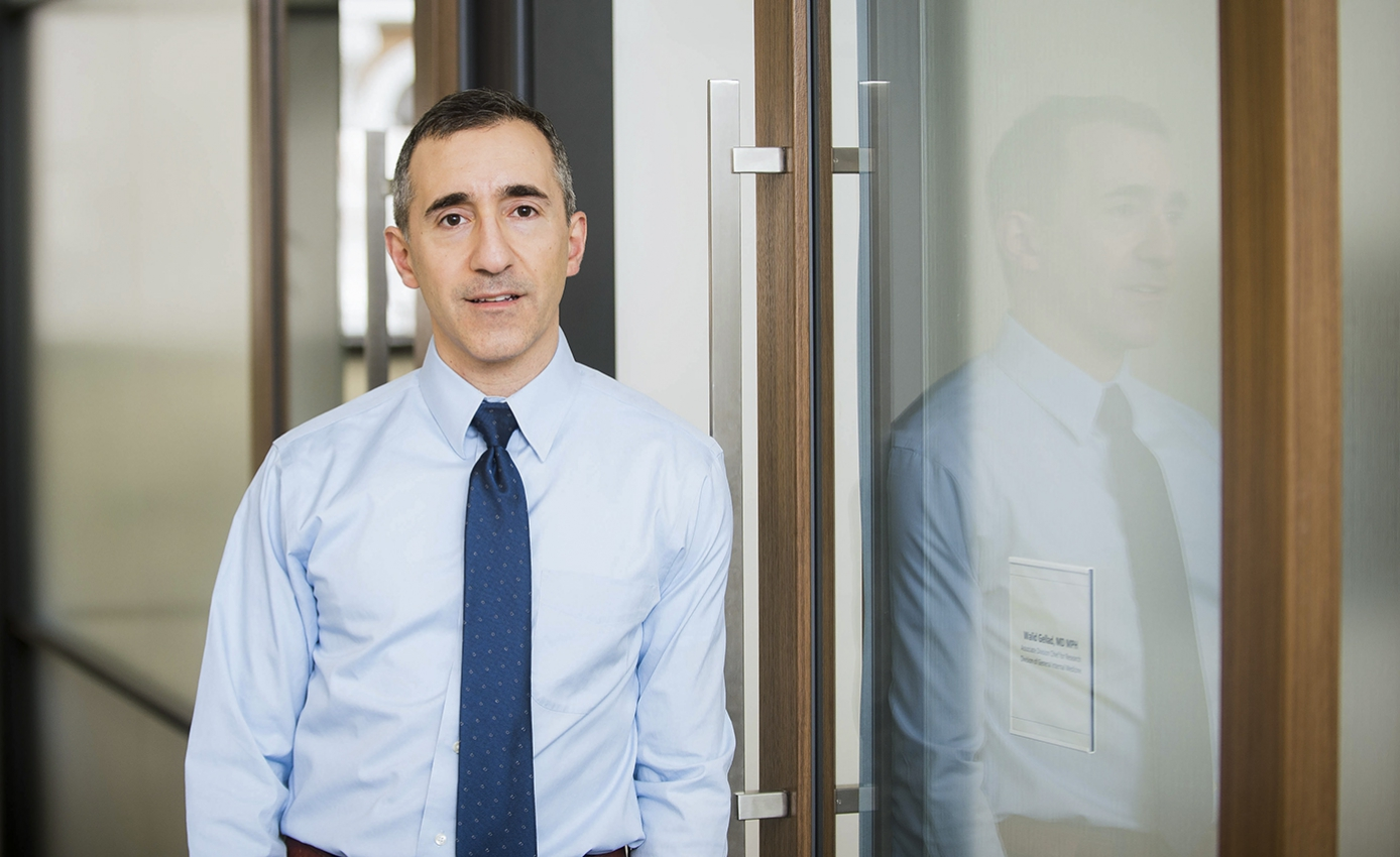 Gellad in a blue shirt and tie in front of a glass wall
