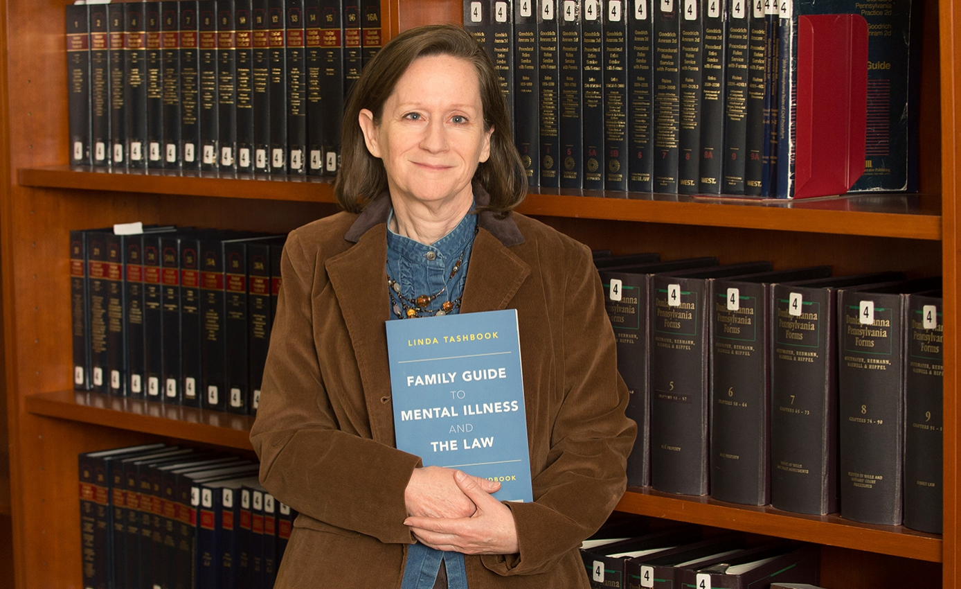 Tashbook standing in front of a large bookcase filled with law volumes, holding her book