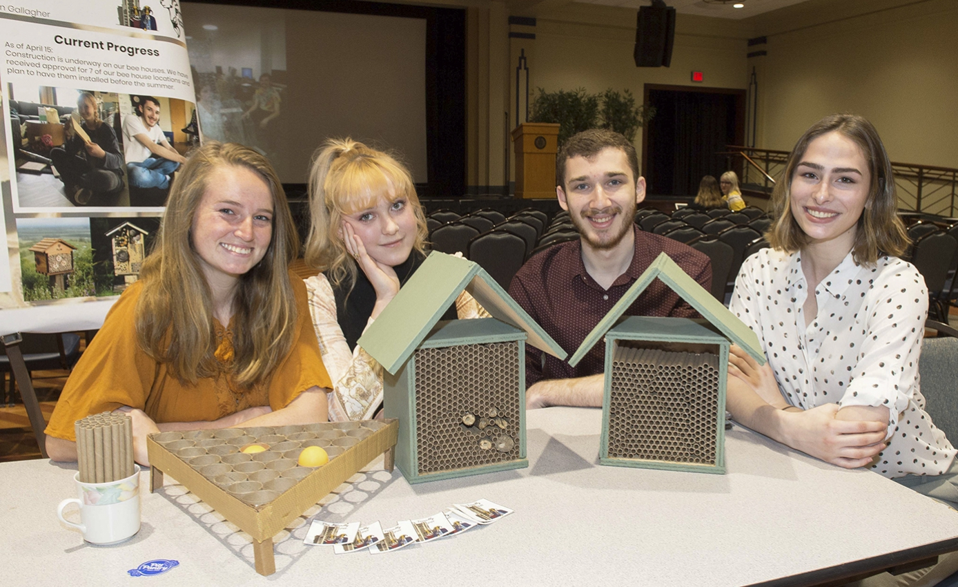 Bee Friendly Pitt teammates Kait Gallagher, Sarah Hart, Matthew Golub and Sarah Cutshall presenting sustainability class project bee houses on a table they are all sitting at