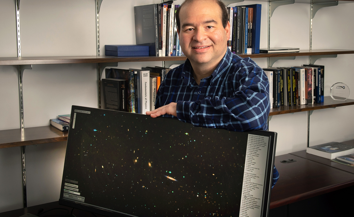 Jeffrey Newman with a monitor displaying stars and galaxies