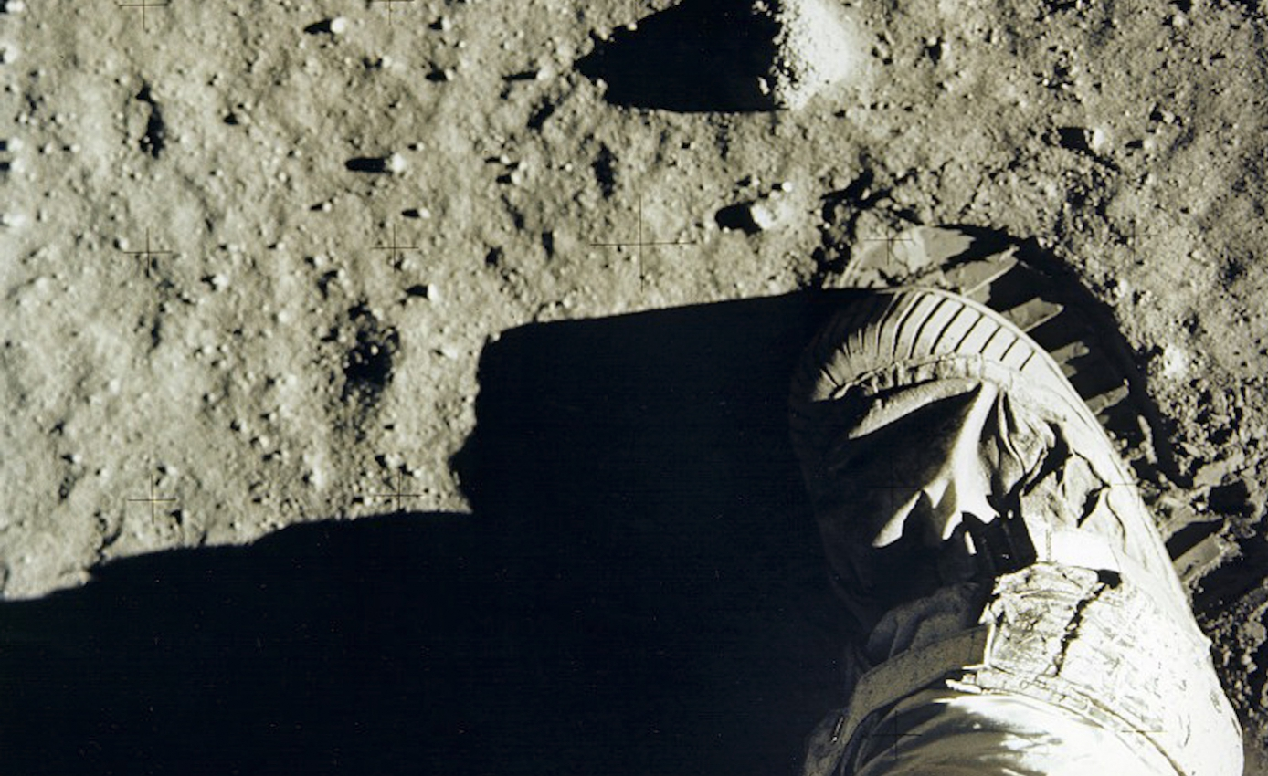 Boot of space suit stepping onto surface of the moon, leaving footprint in soil