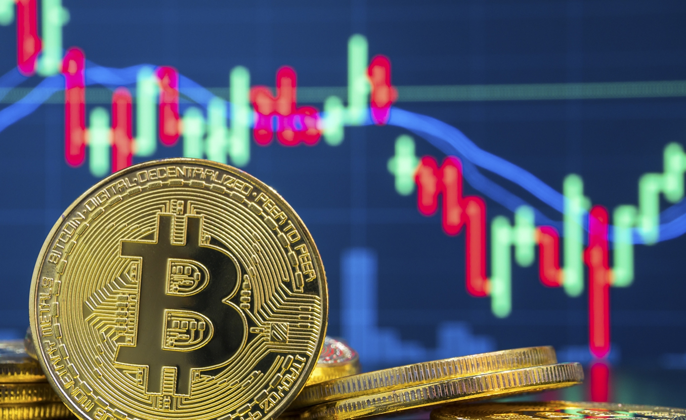 a bitcoin coin in front of a stock market looking graph