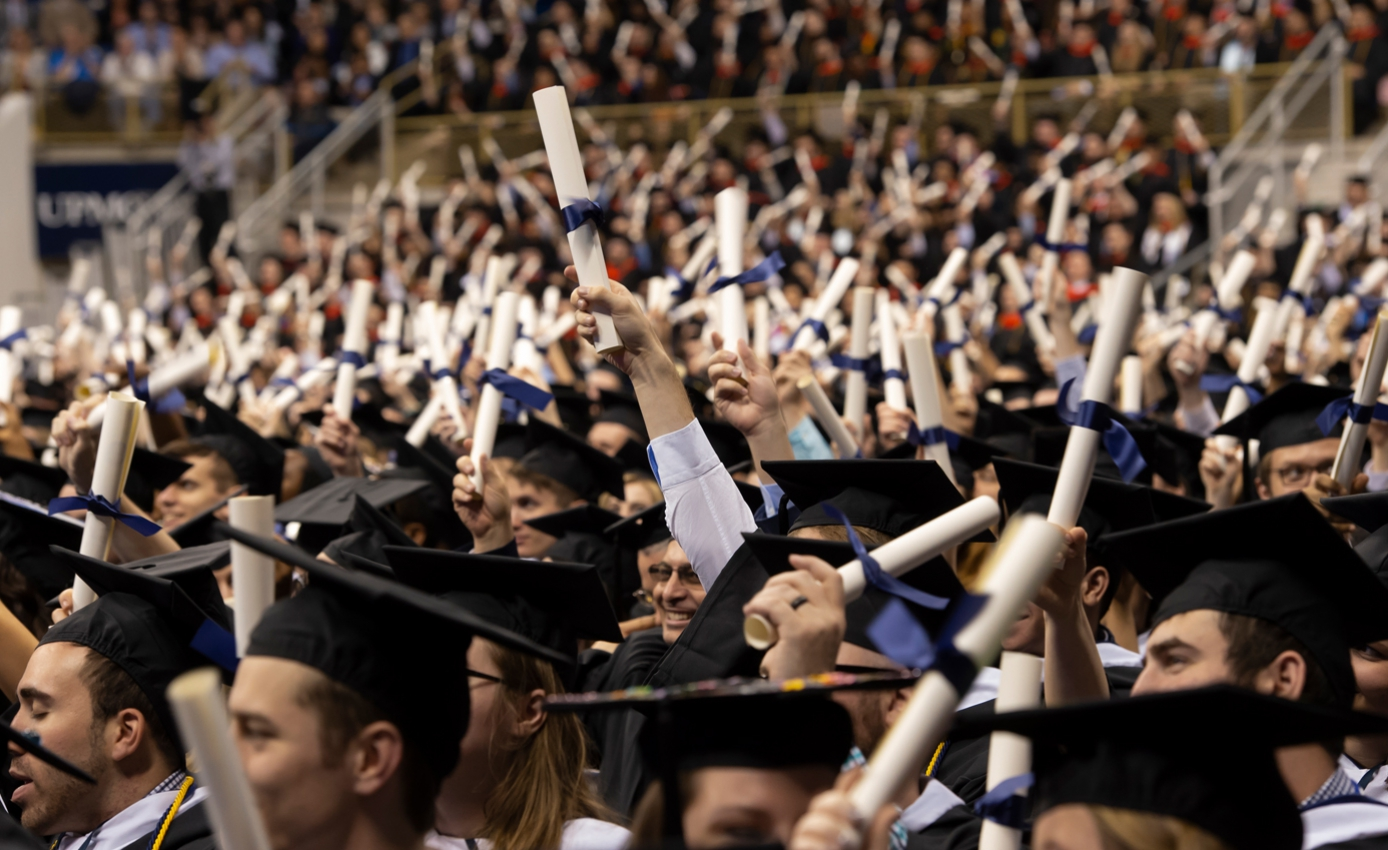 a group of Pitt students in graduation regalia holding up scrolls tied with blue ribbons