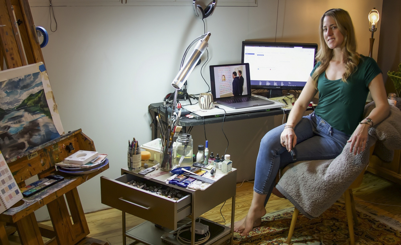 woman in a green shirt in a home office with art supplies