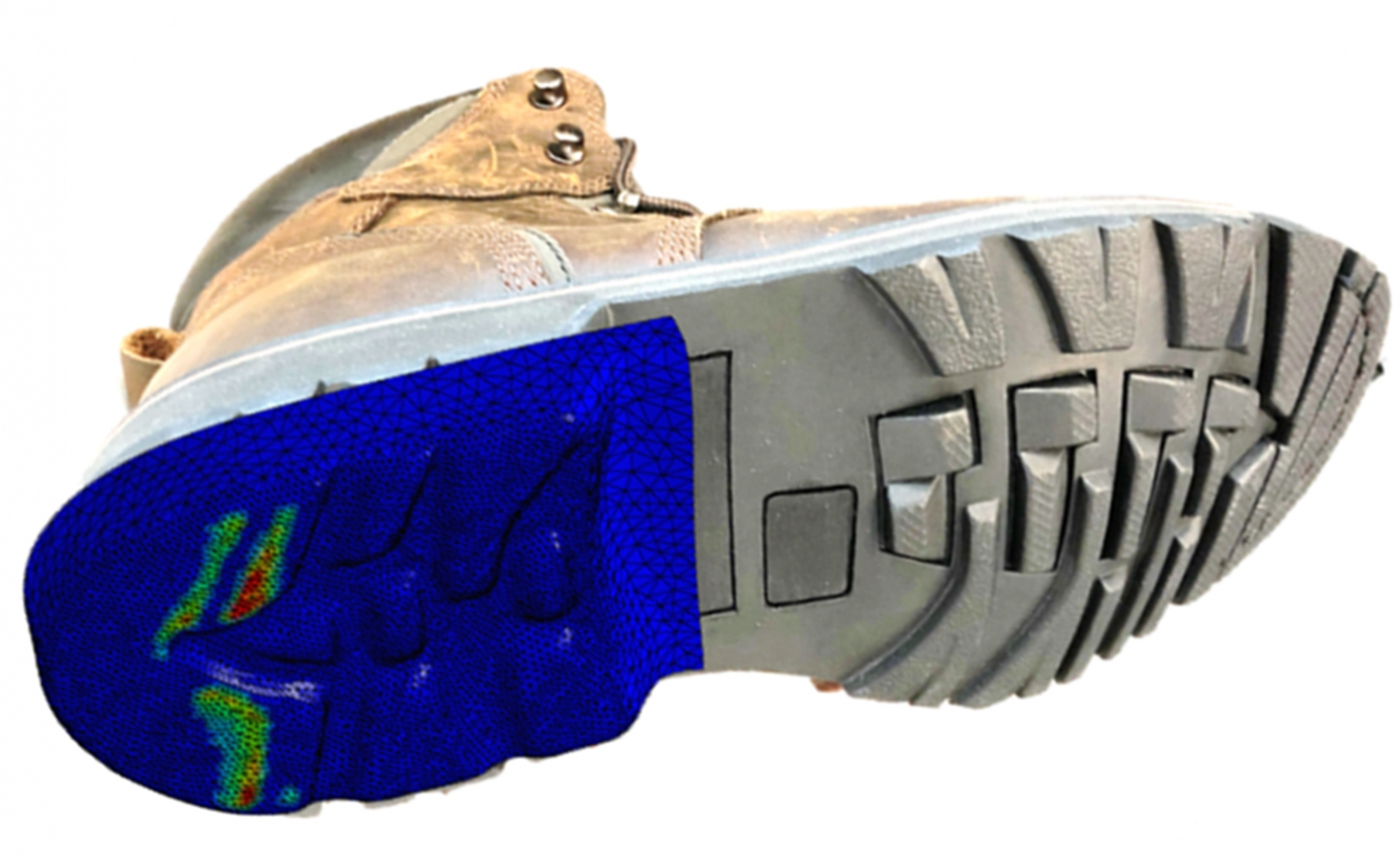 tread of a work boot, the heel of which is a blue, red and green computerized model while the toe is typical gray sole