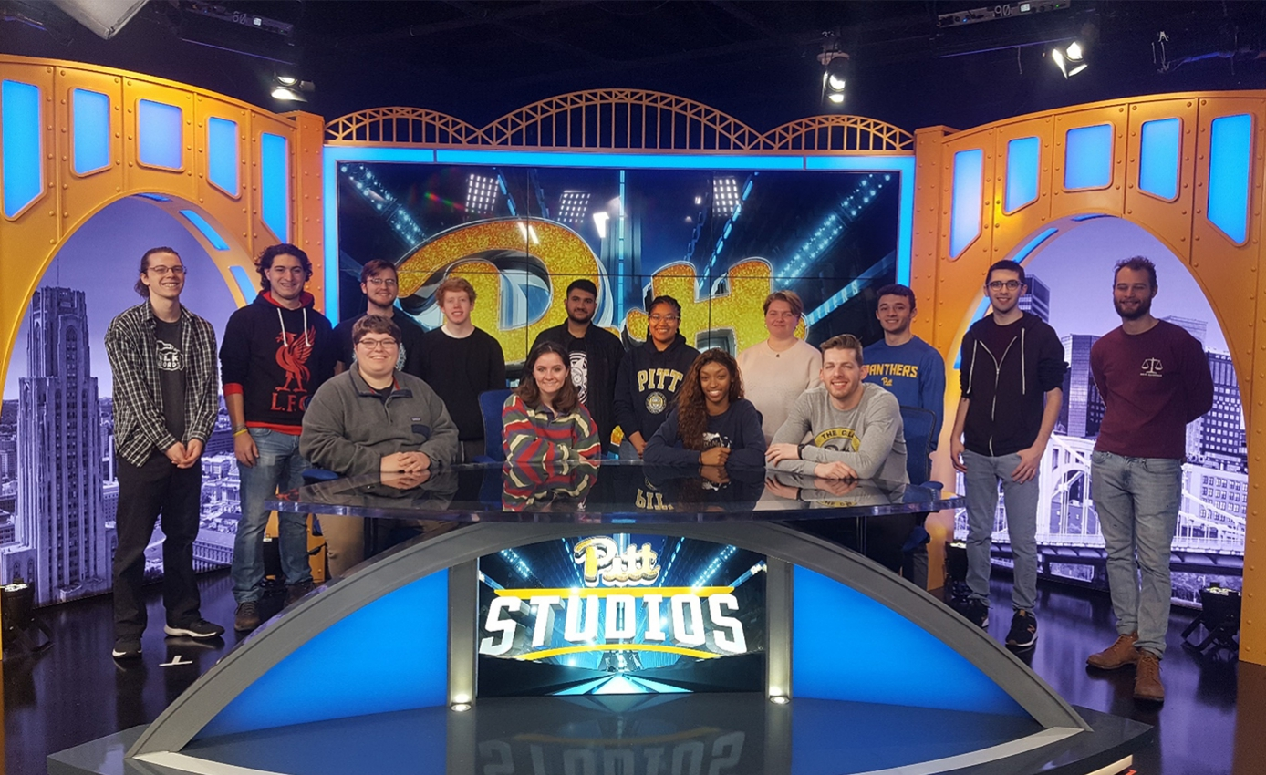 group of students standing and sitting at a news desk in the studios