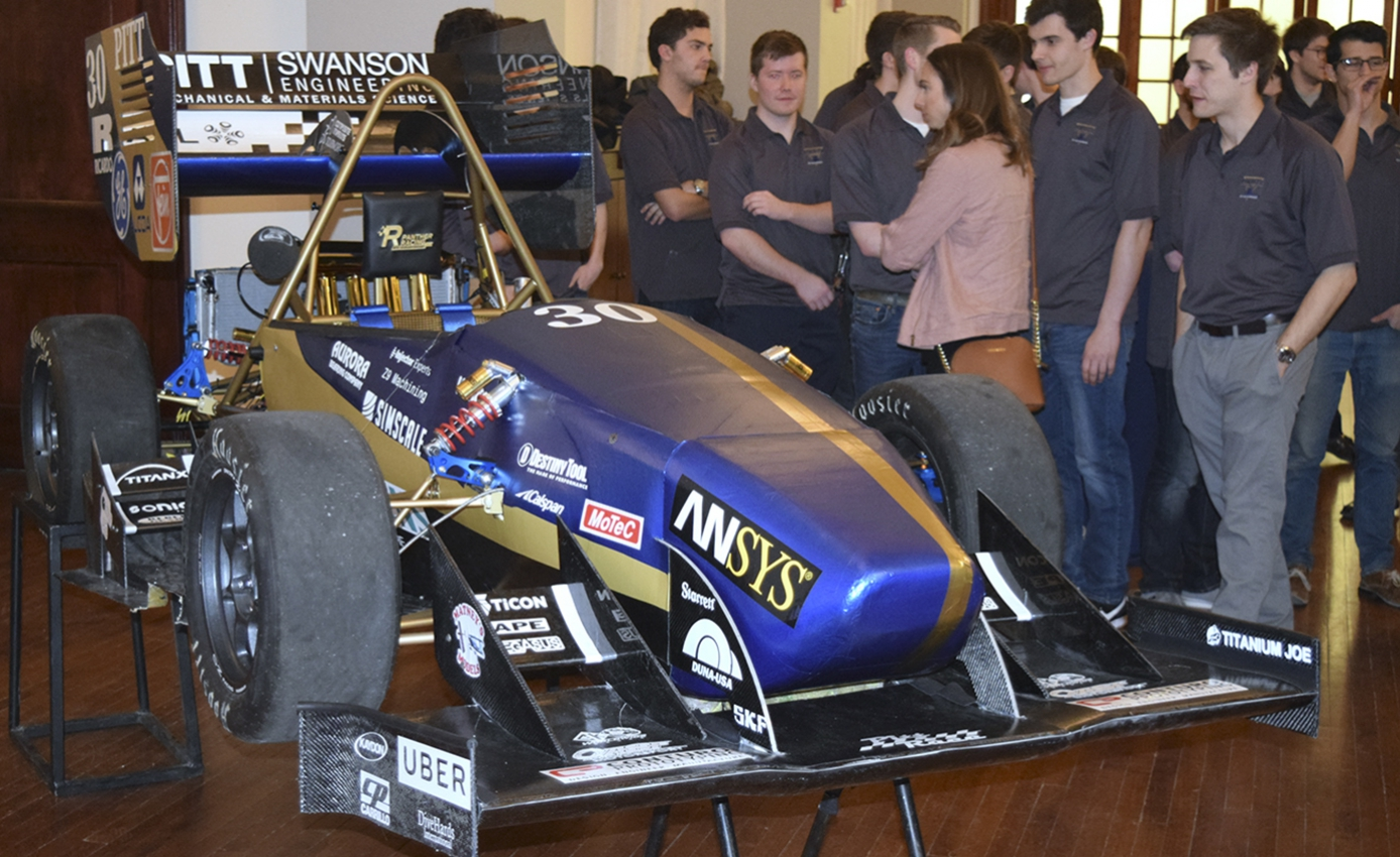 race car in a blue and gold color theme with a crowd of onlookers on the side