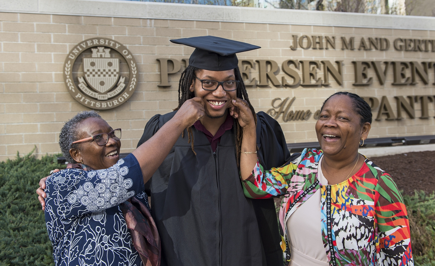 male graduate in cap and gown; his mother and aunt on either side of him, pinching his cheeks