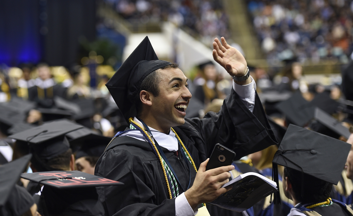 student in a cap and gown smiling, waving