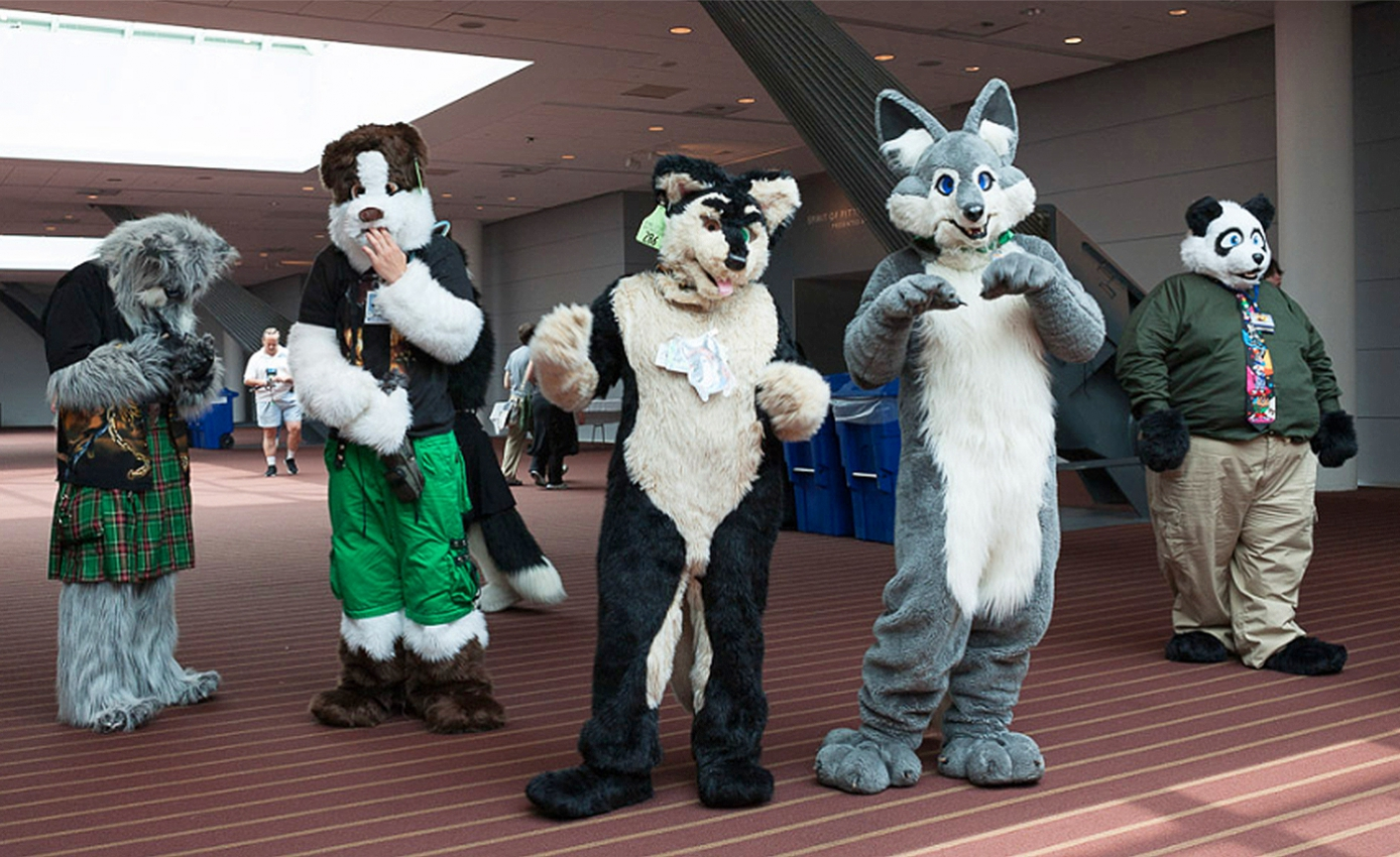 five people in various animal suits in the convention center