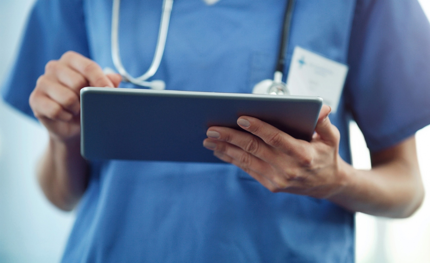 A healthcare professional using a tablet