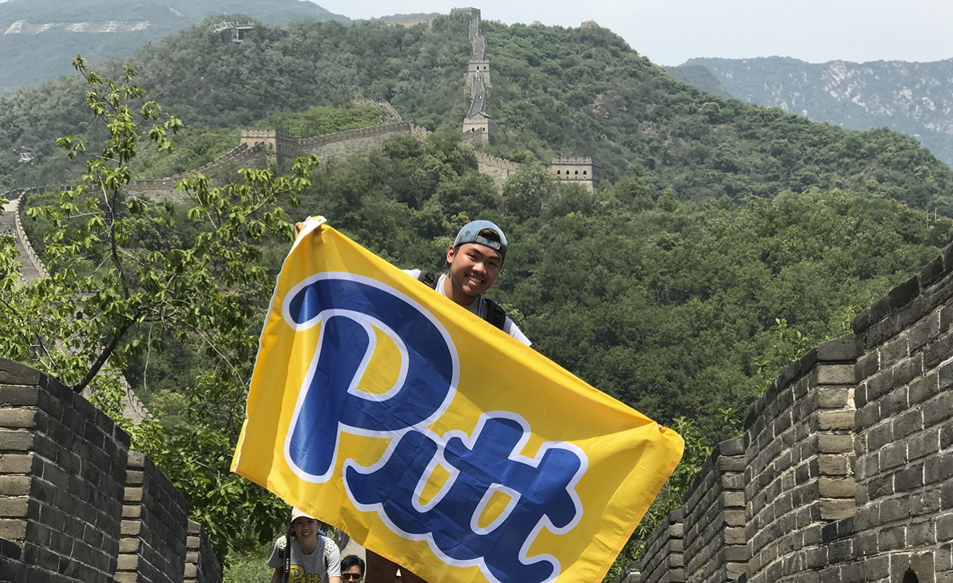 young man in a backwards hat holding a blue and yellow Pitt flag in front of the Great Wall of China