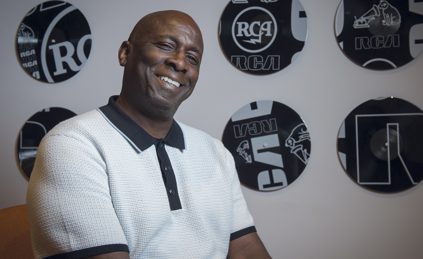 George Bivins head and shoulders shot wearing blue and white polo shirt against RCA promotional background