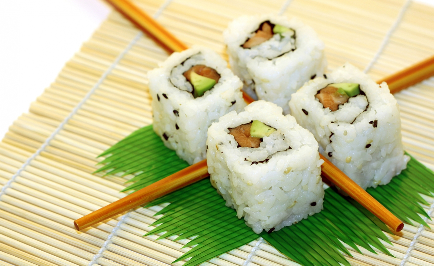 Four rolls of sushi arranged in a square pattern on top of decorative grass