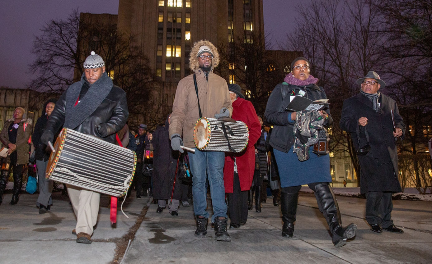 Group of people marching on city street, some carrying drums