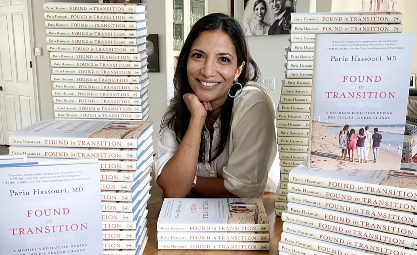 Paria Hassouri in a white top leaning on her elbows on a table with stacks of books