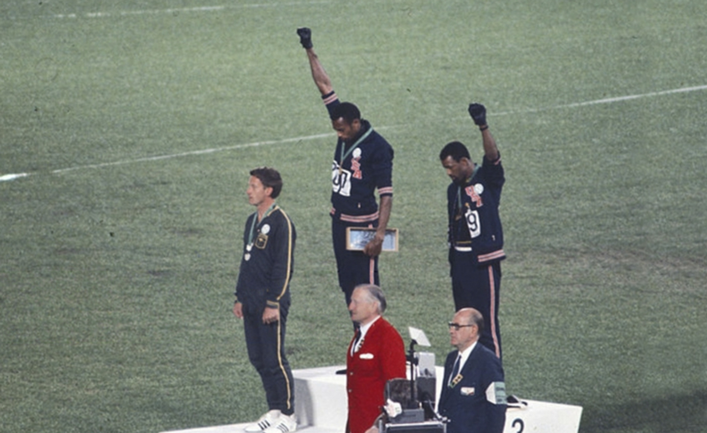 Tommie Smith and John Carlos on a podium holding their fists in the air