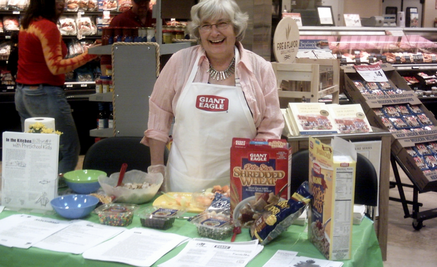 a woman standing at a counter in a grocery store, surrounded by cereal boxes, bowls and papers
