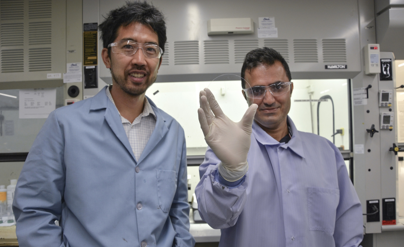 associate professor Paul Leu (left) and doctoral candidate Sajad Haghanifar, both of the Swanson School of Engineering, in blue button down shirts, the latter holding a circle of glass they have developed