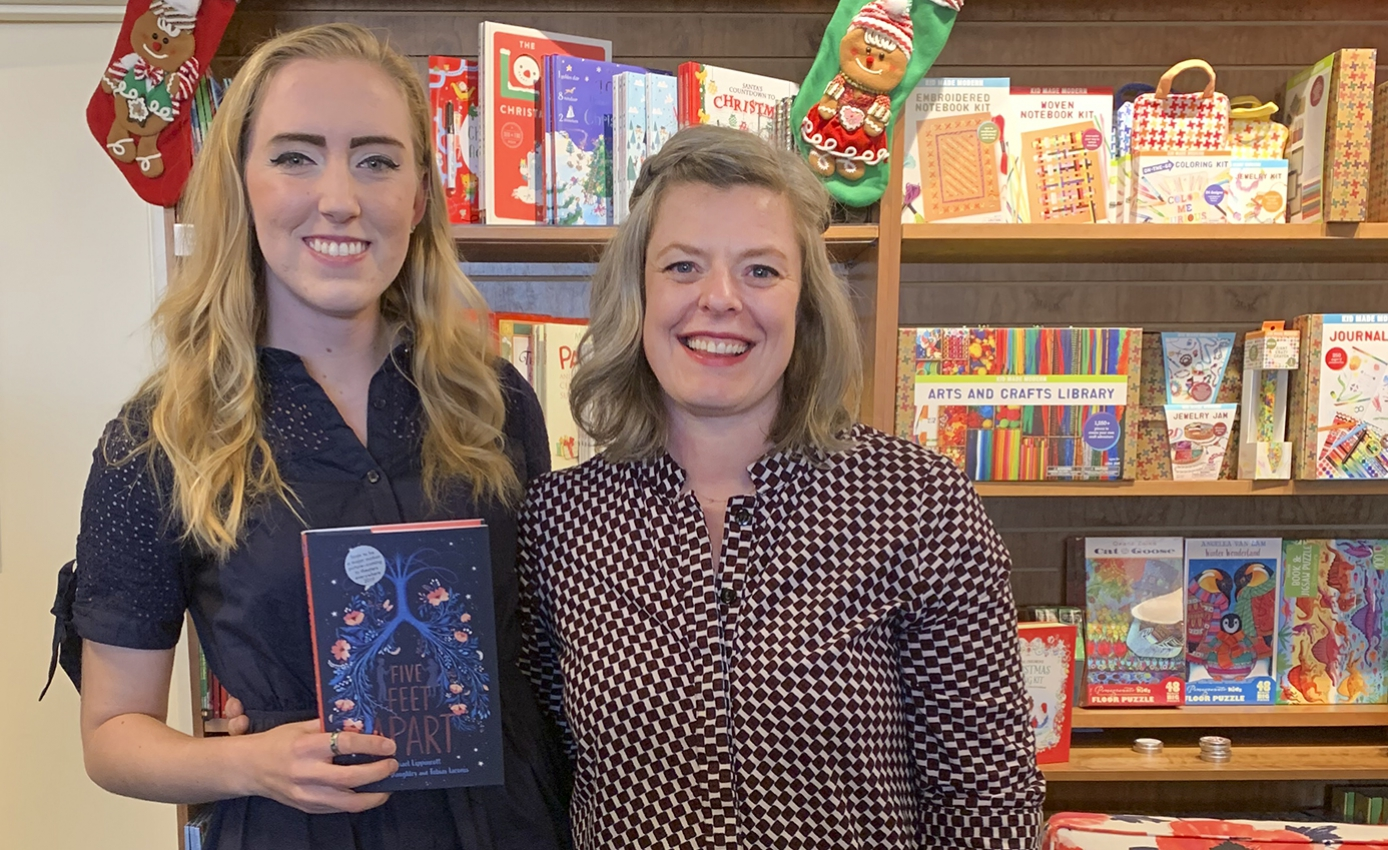 Rachael Lippincott and Siobhan Vivian standing in front of a bookshelf filled with books; Lippincott holds her own book