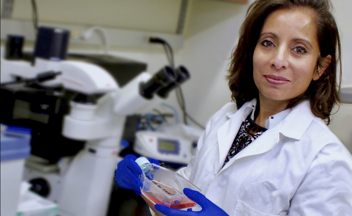Maliha Zahid in white lab coat and wearing blue gloves holding clear bottle of liquid in a lab setting