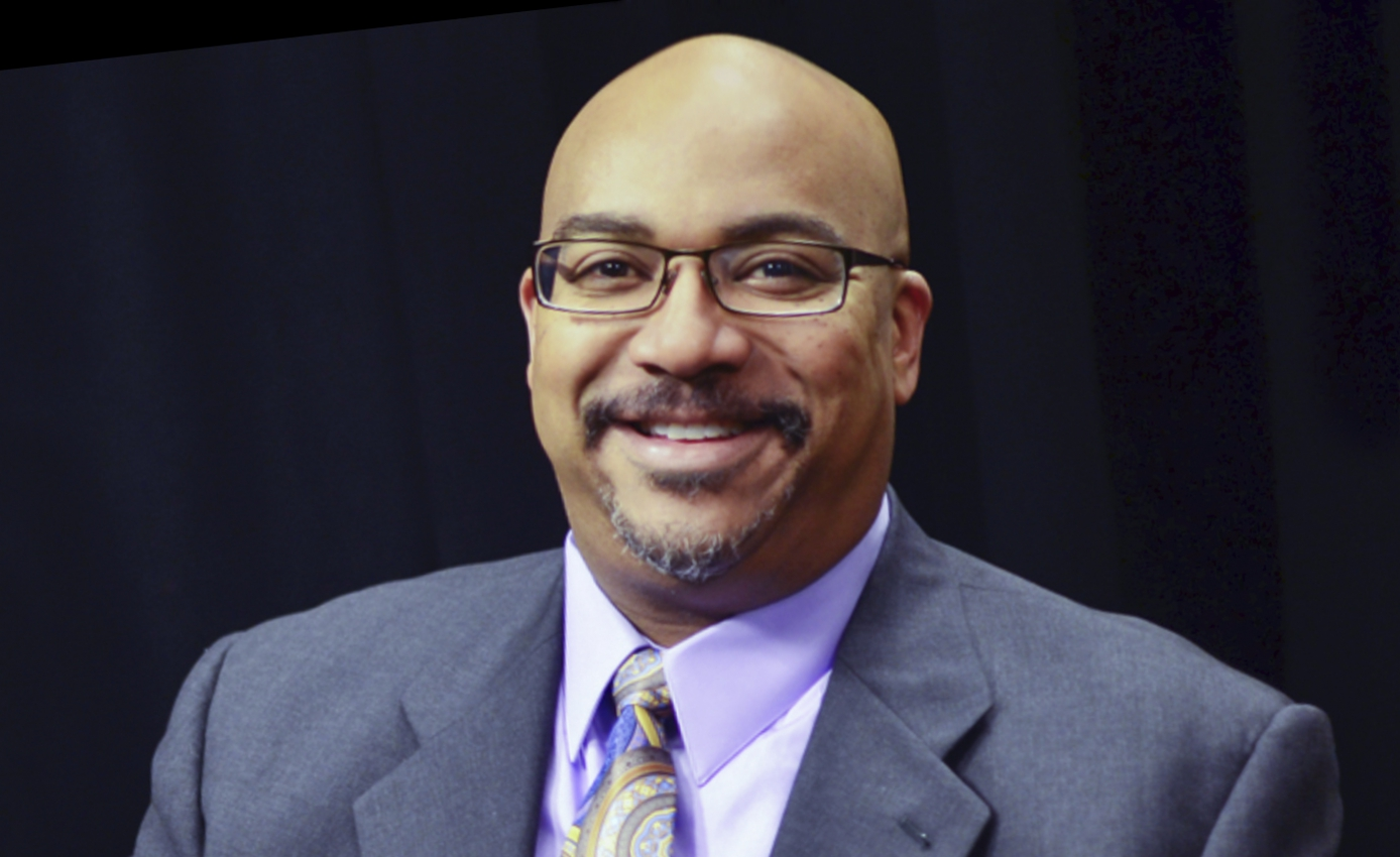 headshot of Mark D. Henderson wearing gray suit jacket, shirt and tie