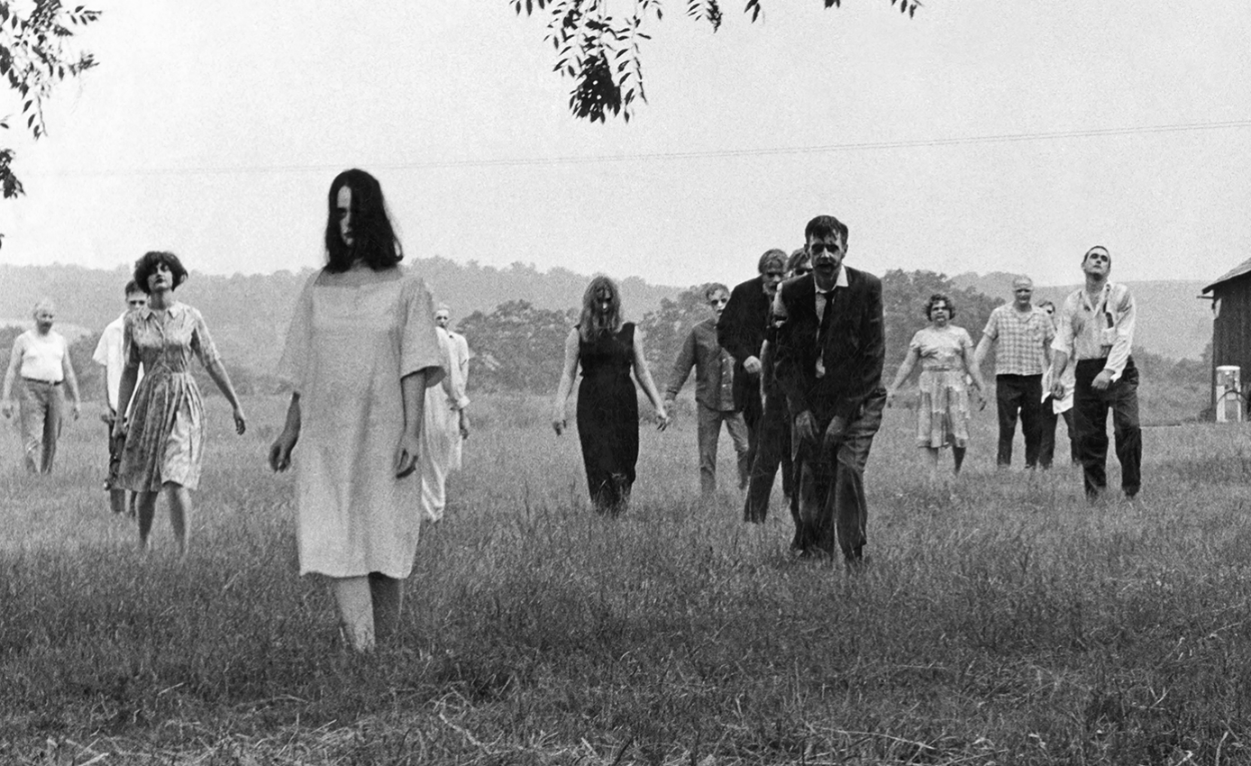 """Black and white film still from """"Night of the Living Dead"""" with several actors portraying zombies walking across a field"""