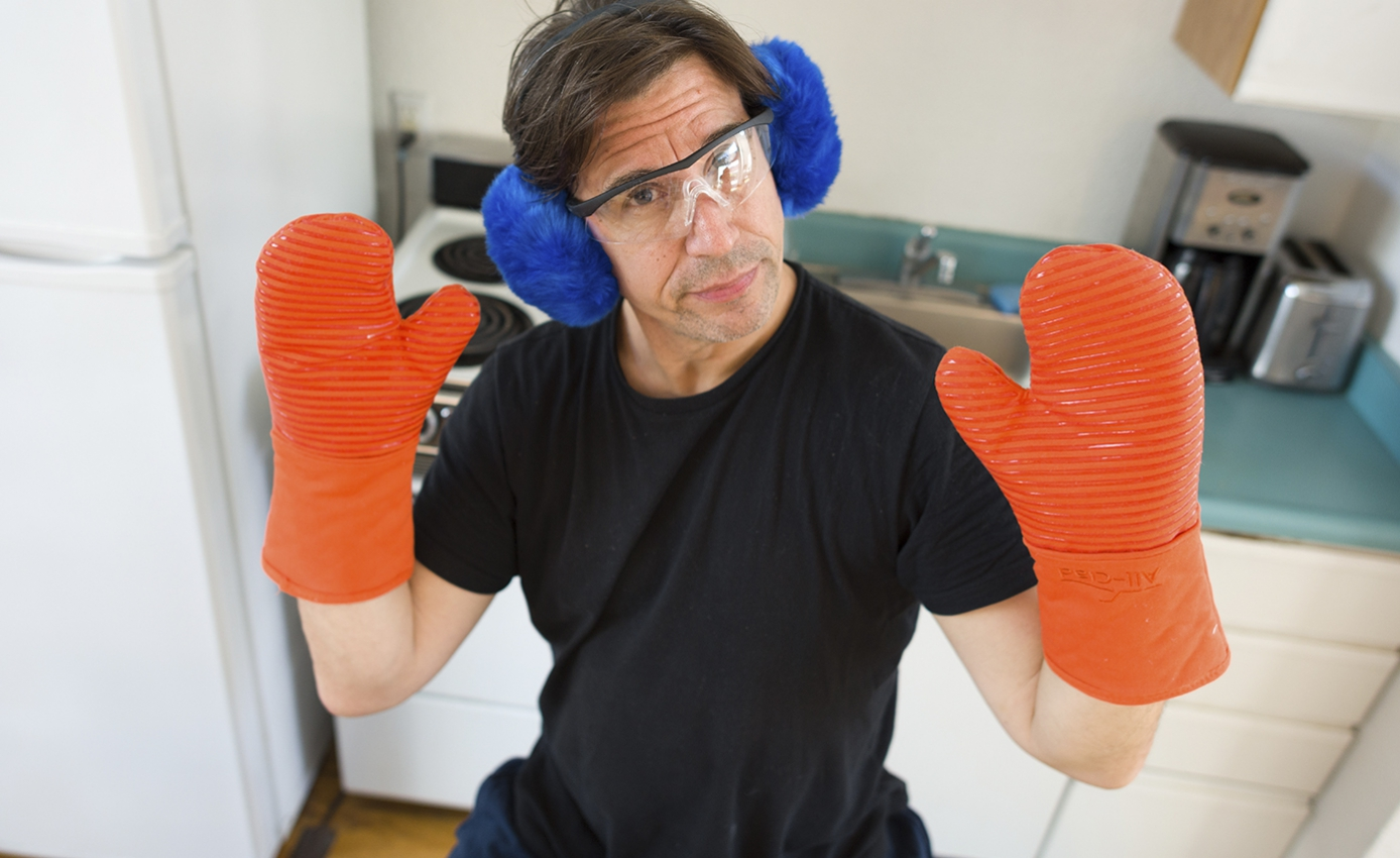 Steve Casner wearing orange oven mitts, blue ear protection and safety glasses