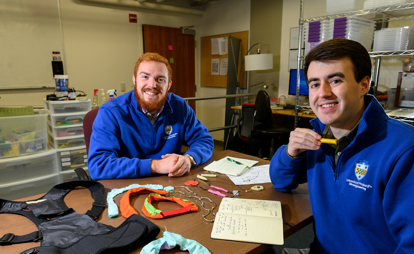 Tyler Bray (left) and Jacob Meadows (right) bioengineering seniors in Pitt's Swanson School of Engineering, in blue Pitt jackets, sitting at a table with their Posture Protect vest on top.