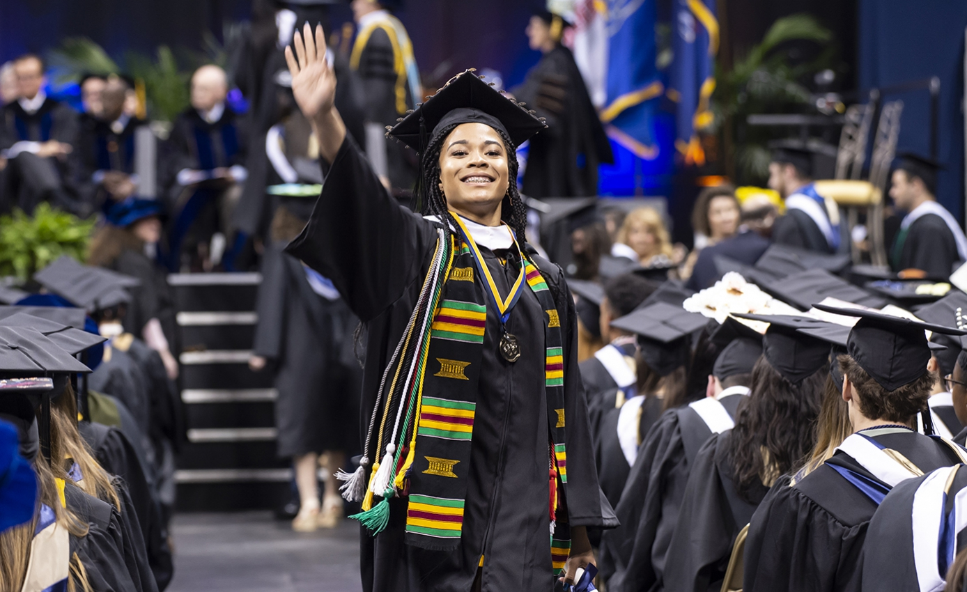 woman in graduation regalia smiling proud and waving