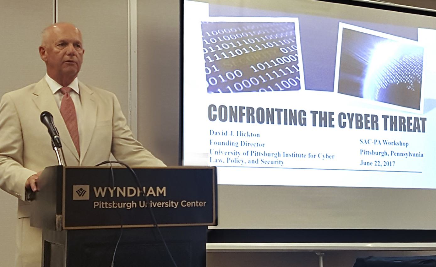 David Hickton in a tan suit standing at a black podium with a slide from a cyber conference projected in the background