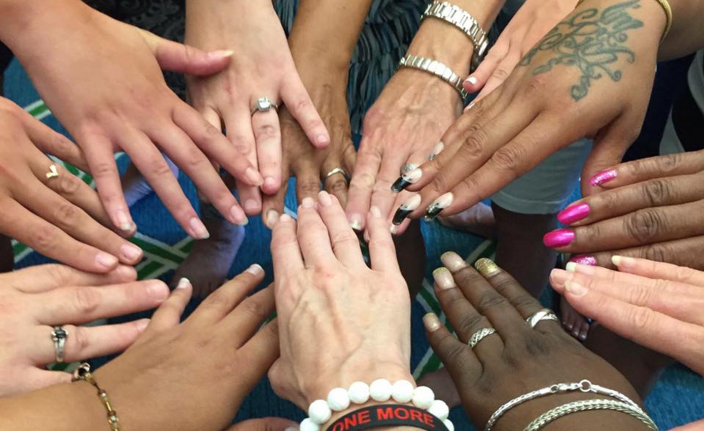 women's hands together in a circle
