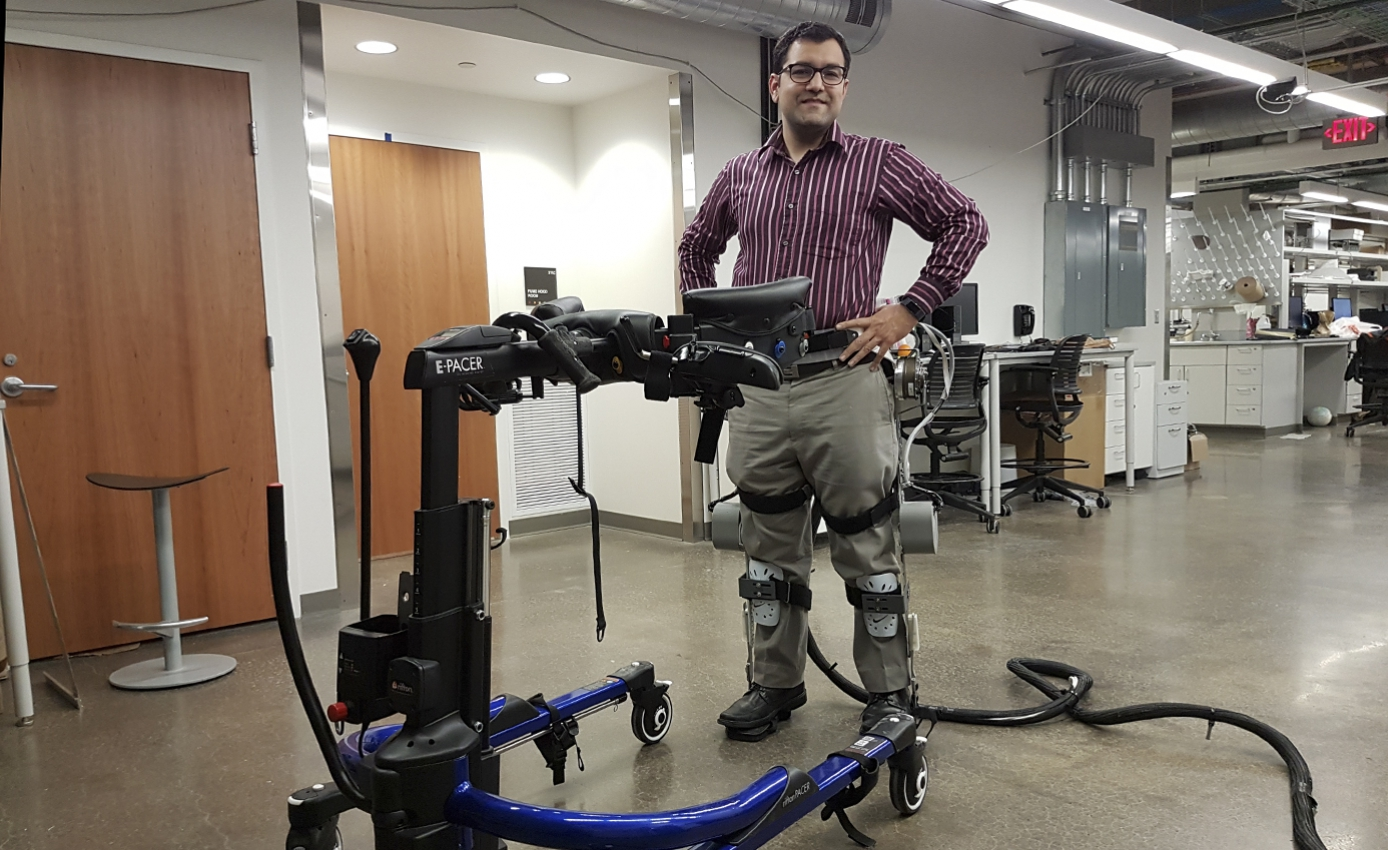 Sharma with his hands on his hips wearing the exoskeleton leg braces