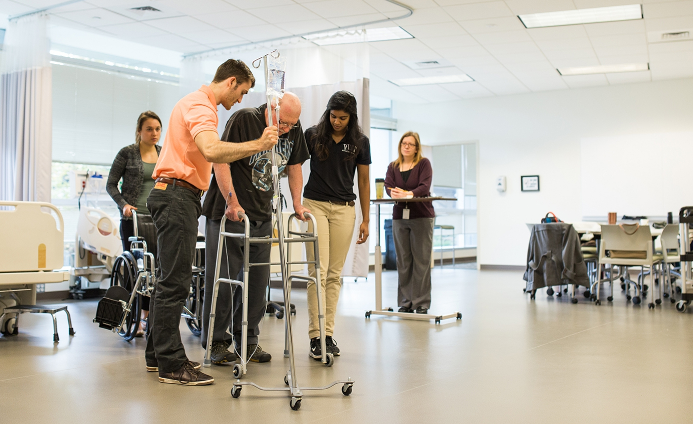 Therapists assist a person in a walker