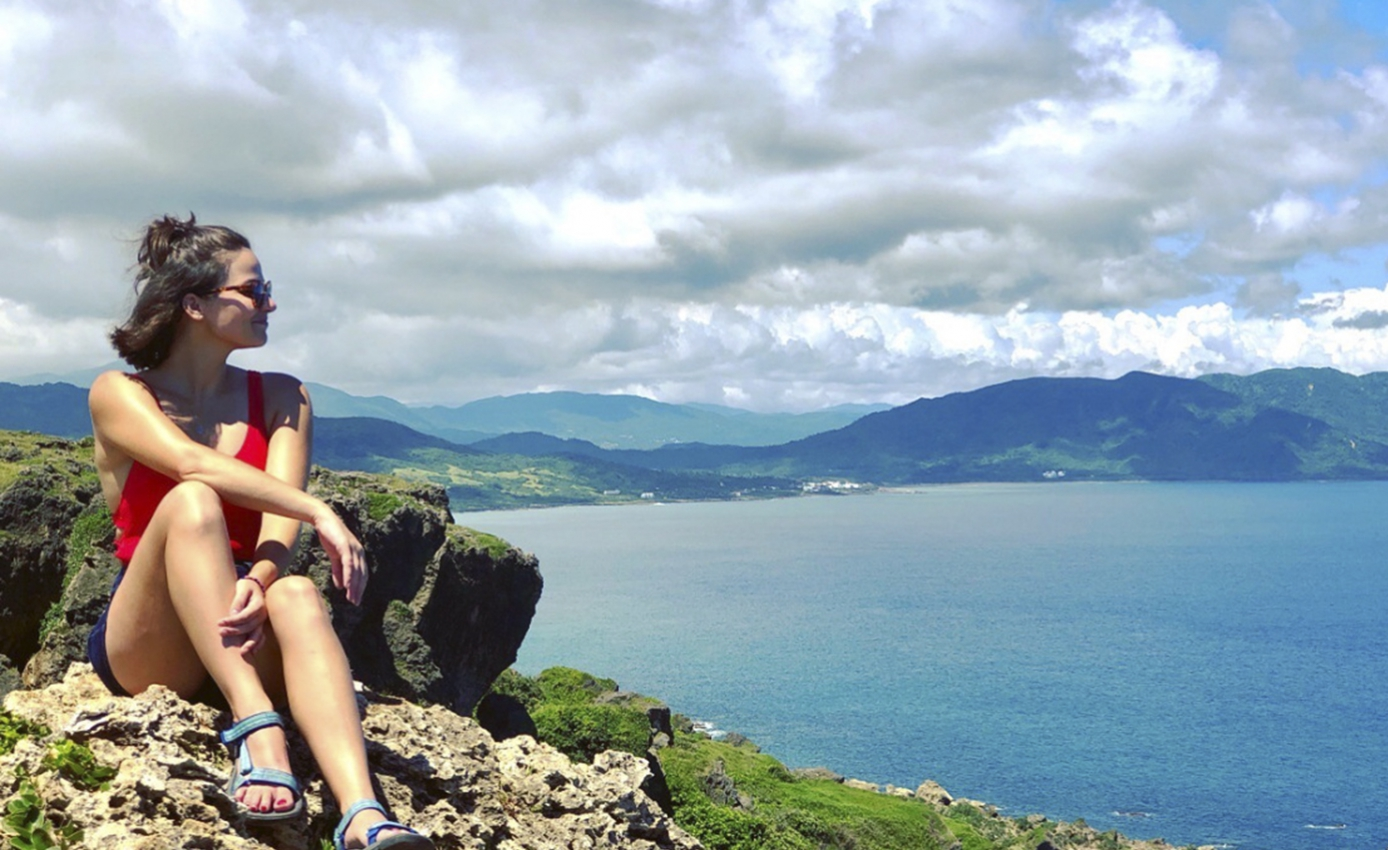 Juliette Rihl in shorts and tank top sitting on rocky ledge overlooking mountains and water, with cloudy sky